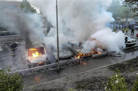 暴動による放火で炎を上げる乗用車